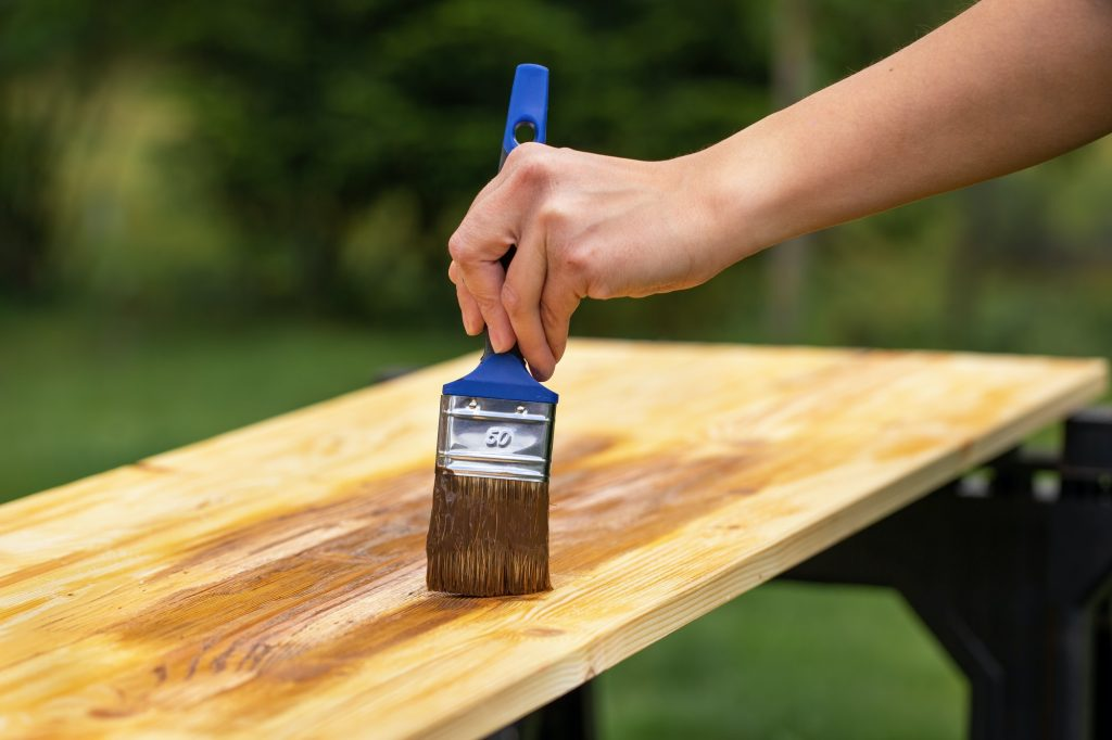 Hand with paintbrush painting a wooden board in garden